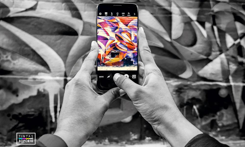 Manos en blanco y negro fotografeando graffiti de color con el móvil